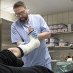 Kuvassa mieshoitaja kipsaa potilaan jalkaa