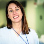 Kasvokuva naistentautien osastonlääkäri Marian Jaalamasta. Kuvassa Jaalama hymyilee sairaalan käytävällä