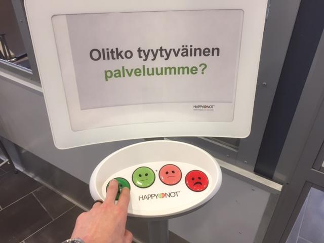 HappyOrNot-mittauslaite, kuvassa sormet painavat vihreintä eli parasta vaihtoehtoa.
