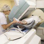 Kuvassa on potilas kuvantamislaitteessa sairaalan työntekijän avustaessa häntä. Kuva on nettikoossa