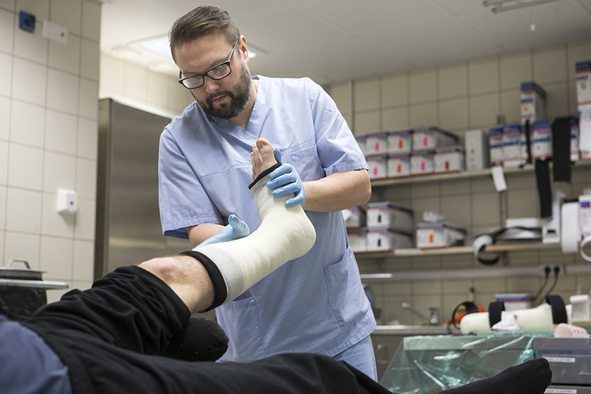 Kuvassa hoitaja tekee kipsiä potilaan jalkaan.