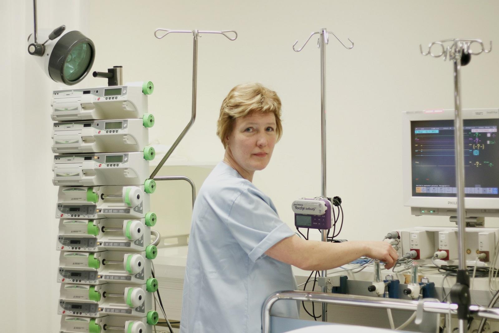 Satu Lukkala työssään erilaisten hoitoon liittyvien laitteiden keskellä.