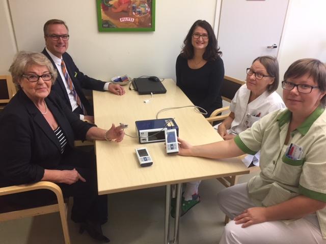 Jukka ja Heli Ylitalo, Sinikka Uola, Laura Aaltonen ja Päivi Kuotola istuvat pöydän ääressä, jolle on asetettu pulssioksimetrit.