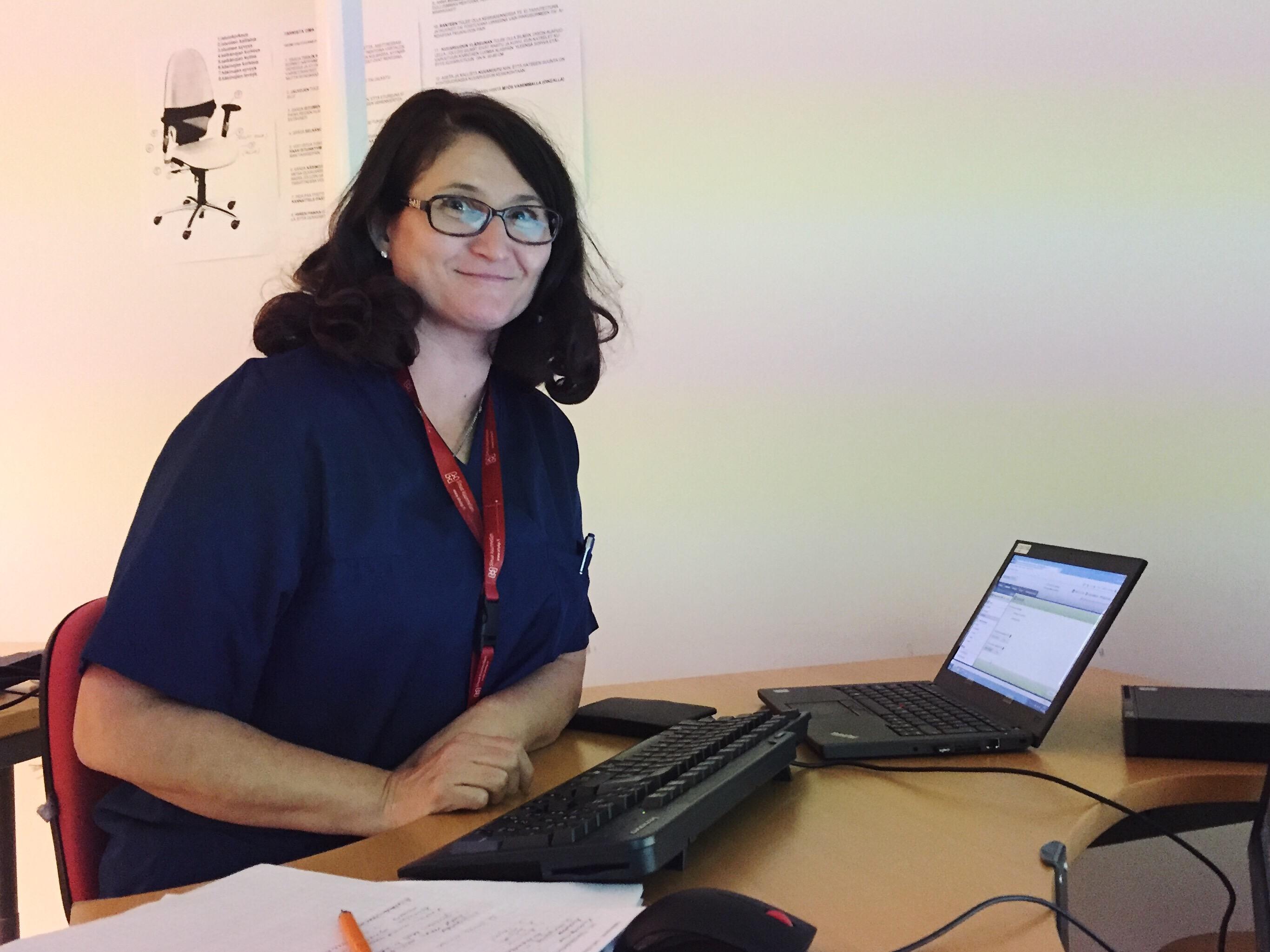 Heli Ylitalo katsoo kameraan istuessaan työpöydän ääressä.