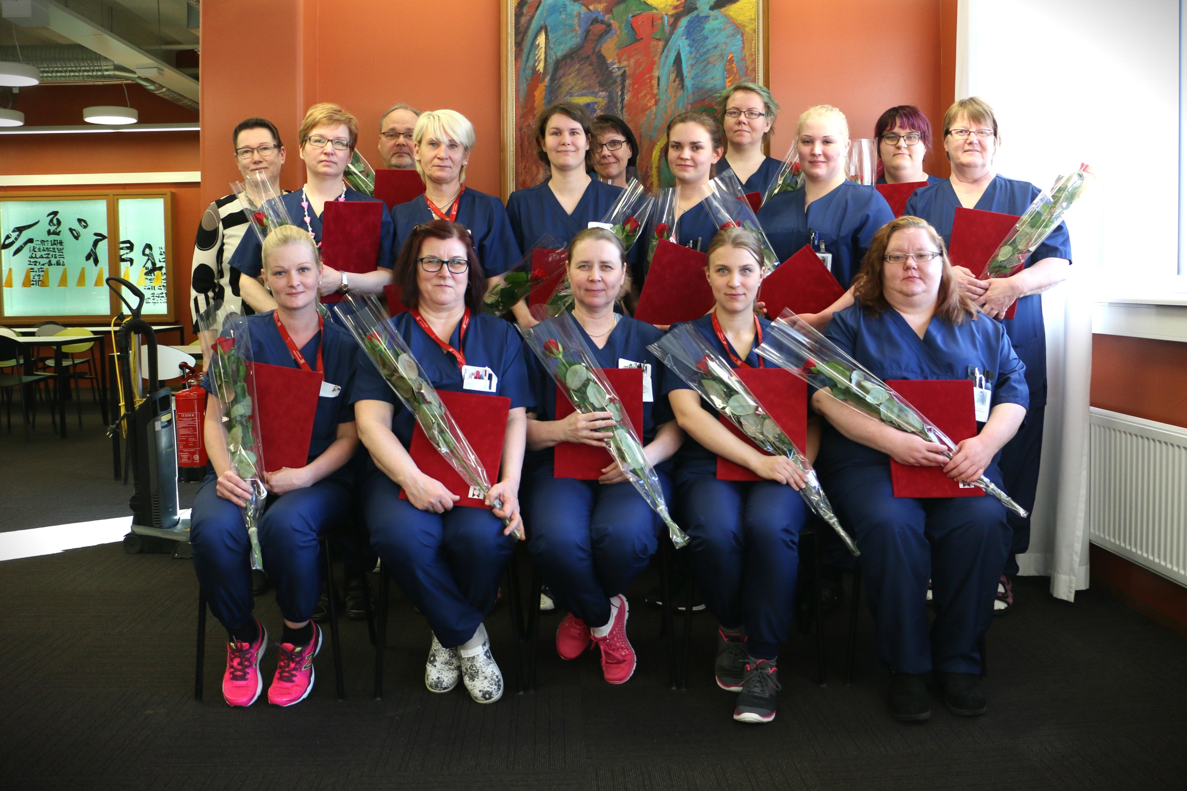 Kanta-Hämeen ensimmäiset oppisopimuksella kouluttautuneet sairaalahuoltajat ryhmäkuvassa todistuksiensa ja ruusujen kanssa.