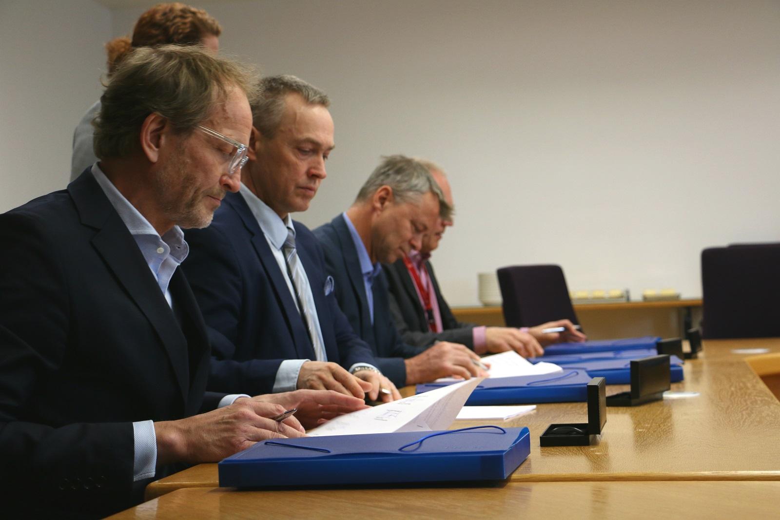 Matti Anttila, Tuomas Särkilahti, Markku Varis ja Hannu Juvonen allekirjoittamassa sopimusta rivissä.