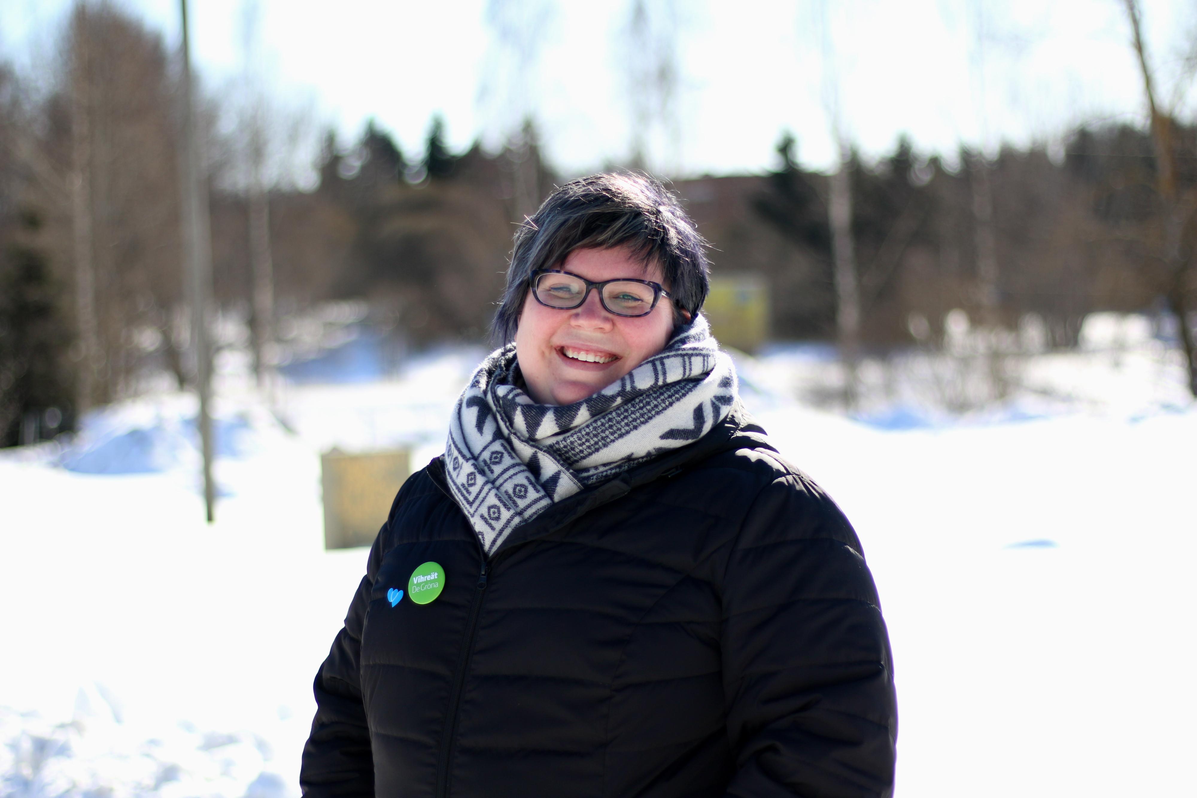 Satu Heinonen katsoo hymyillen kameraan. Kuva on otettu ulkona talvella.