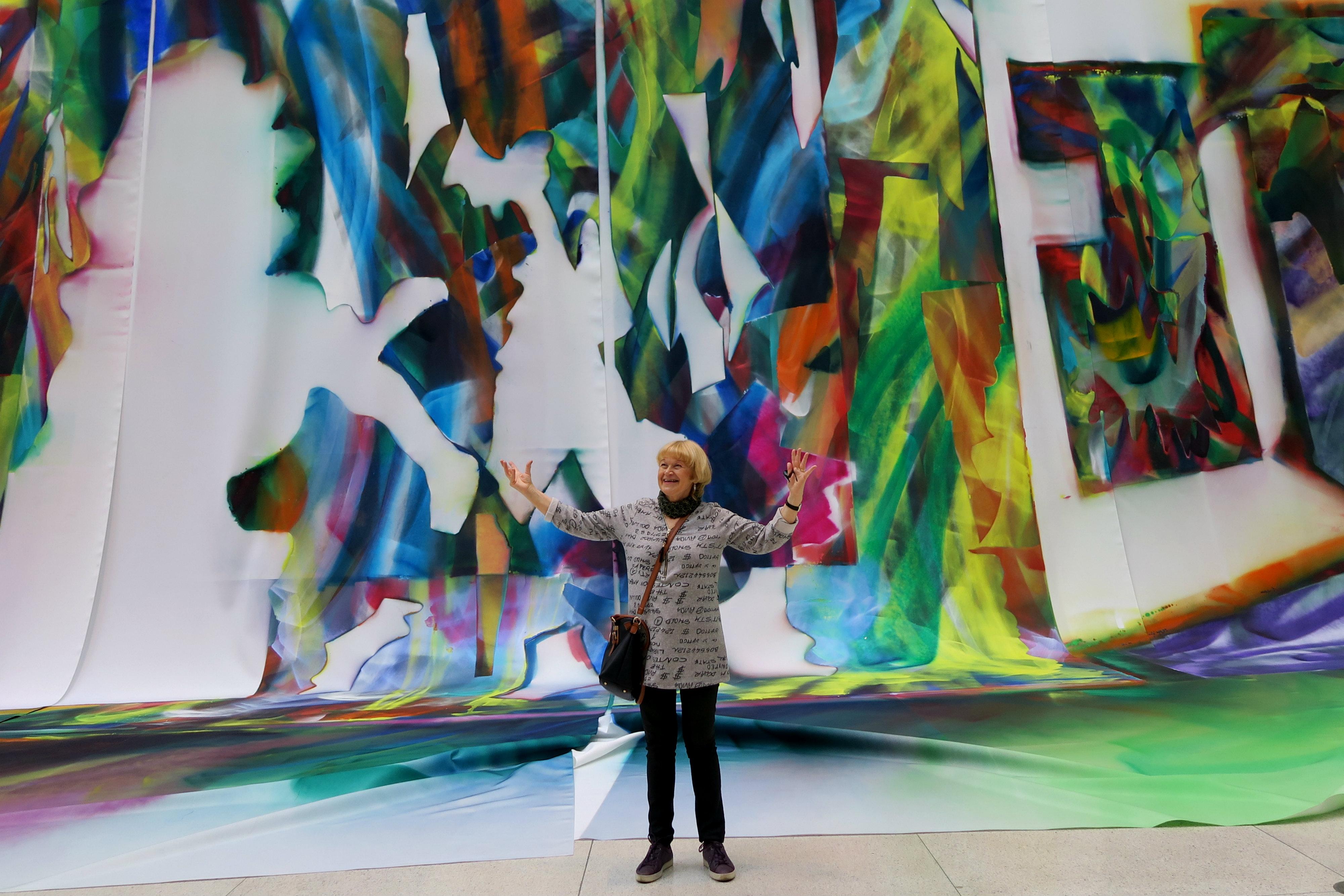 Anne Rekola seisoo iloisena kädet levällään värikkäänt taideteoksen edessä.