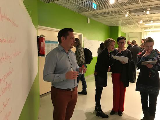 Tampere-talolla järjestetyssä työpajassa Petrus Kukkonen ja muita henkilöitä seisoo fläppitaulun edessä, jolle on kirjattu useita asioita.