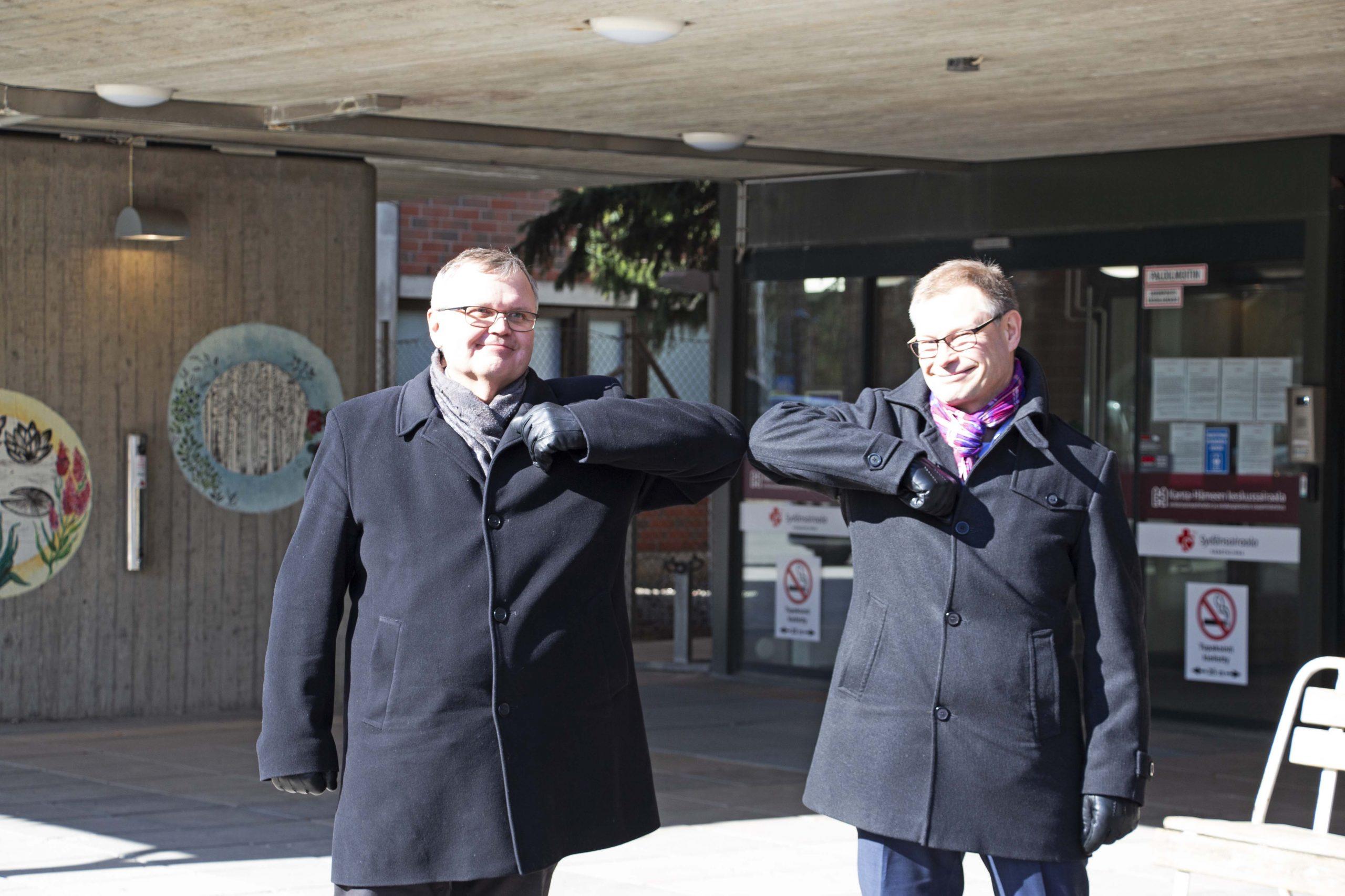 Seppo Ranta ja Mika Helin tekevät ns. koronatervehdyksen eli lyövät kyynärpäitä yhteen.
