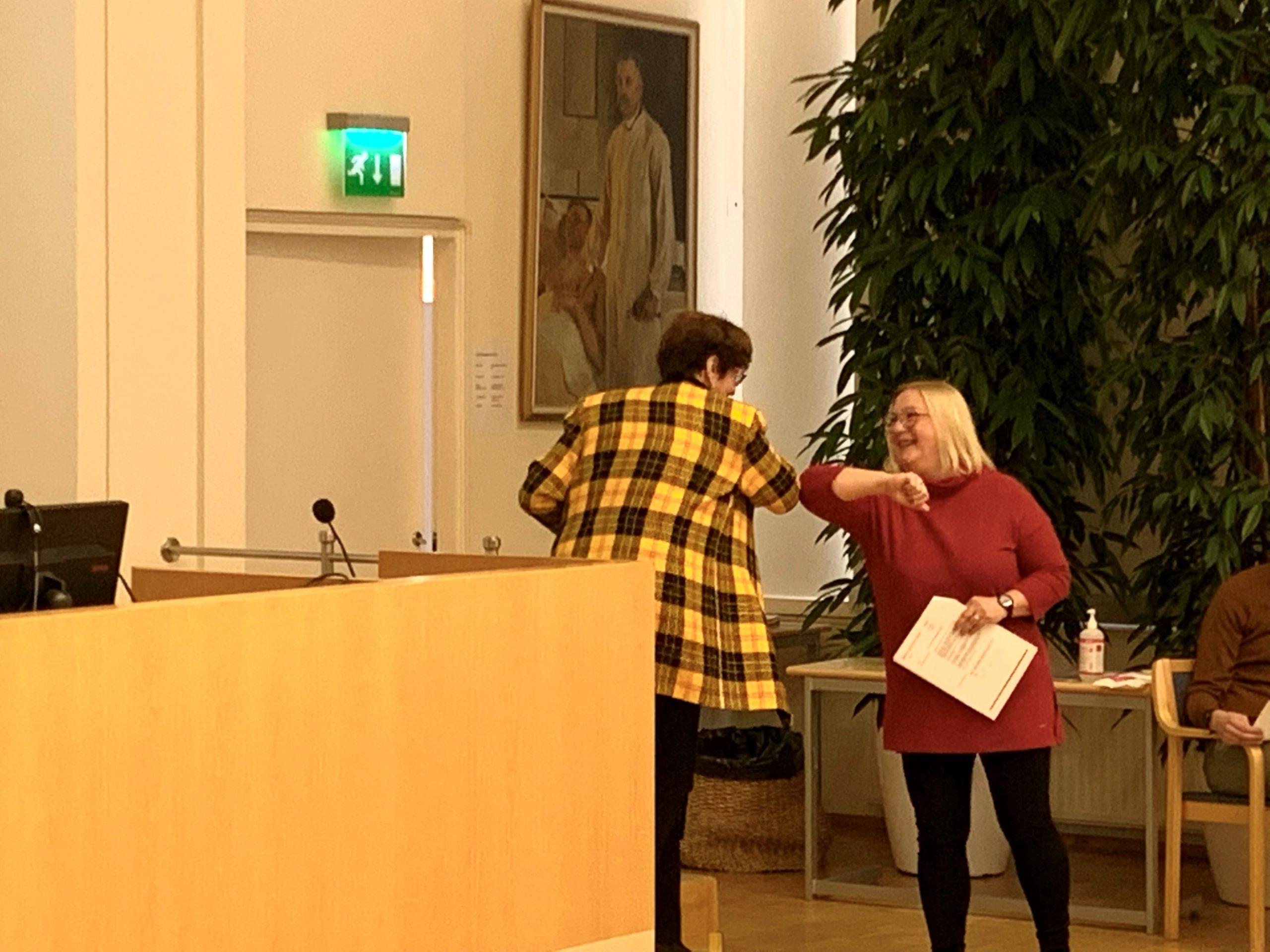 Valtuuston ikäpresidentti Sirkka-Liisa Anttila ja uusi puheenjohtaja Sari Myllykangas koronatervehtivät toisiaan.